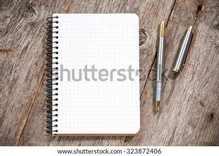 Fountain pen and notebook with square grid on wooden surface - stock photo