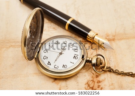 fountain pen and pocketwatch on old parchment - stock photo