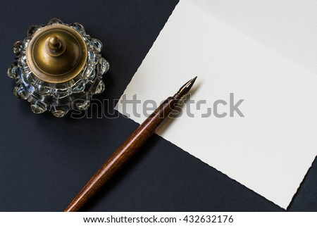 Fountain pen, inkwell, letter on a black background - stock photo