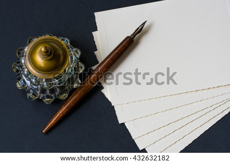Fountain pen, inkwell, papers on a black textured - stock photo