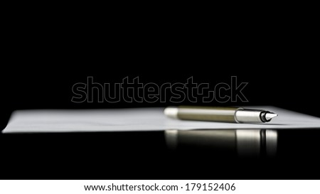 Fountain pen lying on a document depicting writing a letter, taking notes or signing a document, isolated over black background. - stock photo