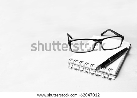 Fountain pen notebook and glasses in composition in black and white - stock photo