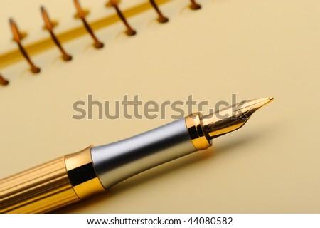 Fountain pen on a yellow notebook. Selective focus - stock photo
