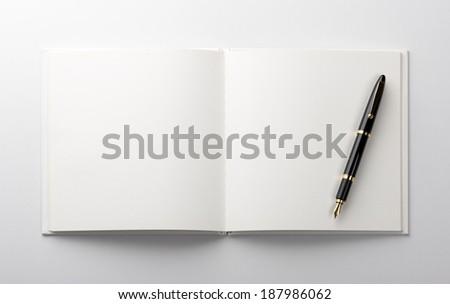 fountain pen on blank book - stock photo