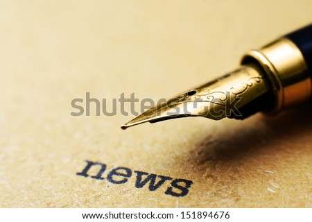 Fountain pen on news text - stock photo