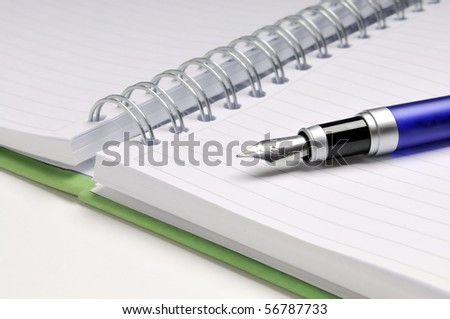 Fountain pen on notebook - stock photo