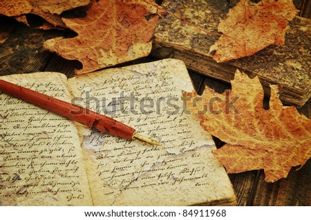 Fountain pen on old handwritten book with autumn leaves - stock photo