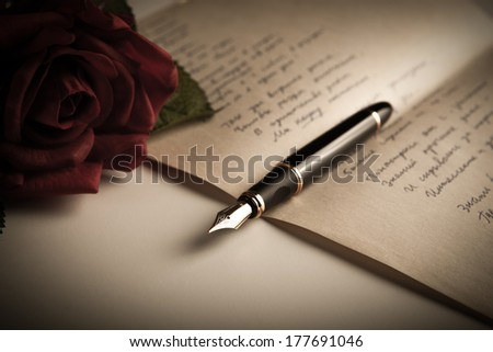 fountain pen on text sheet paper with rose close-up