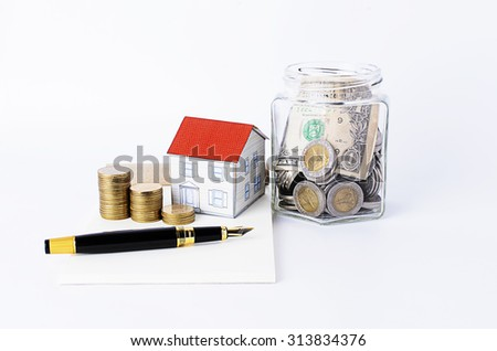Fountain pen with coins stack and paper house and bottles bank