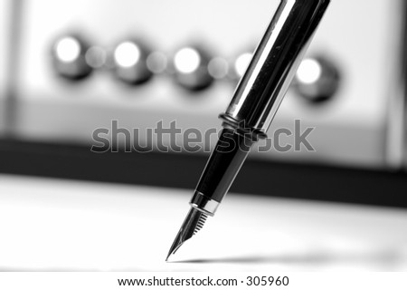 Fountain Pen With Newtons Balls in Background - stock photo