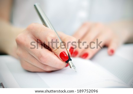 fountain pen writing or signing on a diary - stock photo