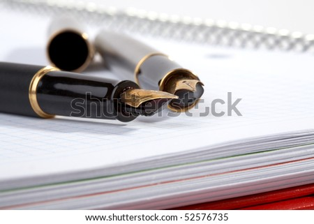 fountain pens lays on a writing-book with spiral - stock photo