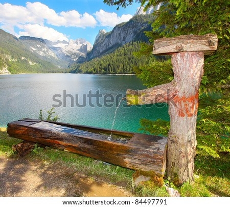 Fountain with drinking water over a Vorderer Gosausee alpine mountain lake in Salzkammergut, Austria, Europe. - stock photo