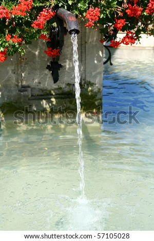 Fountain with red flowers on a hot summer day - stock photo