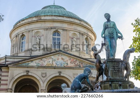 Fountain with statues in front of old domed building - stock photo