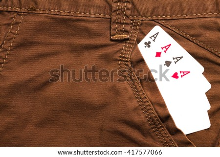 four ace cards inside brown jeans front pocket closeup