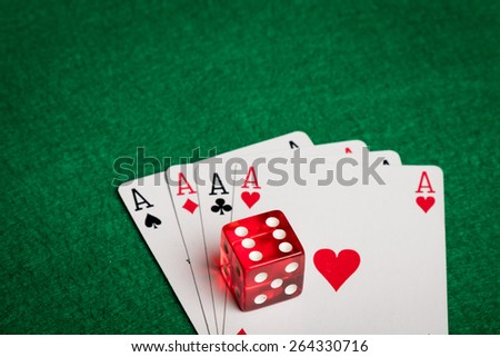 four aces and a red dice on a green table - stock photo