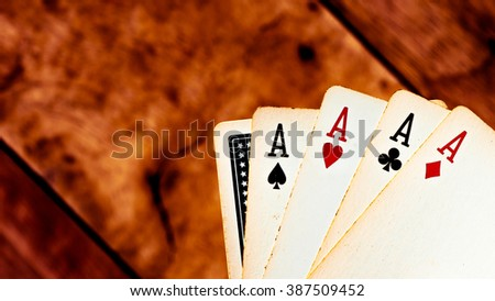 four aces and hide card poker game playing cards on a weathered wood table in an old western frontier gambling establishment saloon vintage color tone style / winner - stock photo