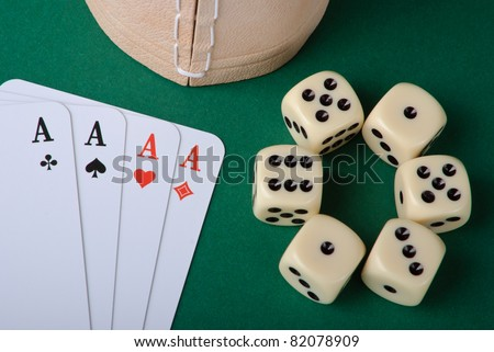 Four aces and six dices with cup on green background - stock photo