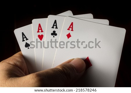 Four Aces cards in hand for play gamble.  - stock photo
