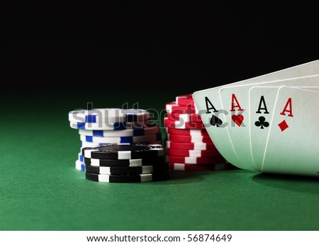four aces high on green table with chips on black background - stock photo