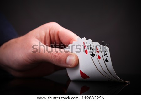 Four aces in the hand on black background - stock photo