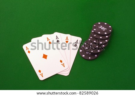Four aces near some black chips over green carpet