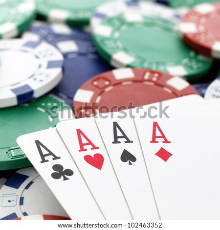 four aces of a kind with chips background