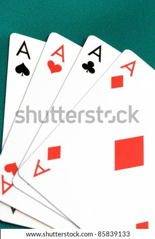 Four aces playing cards close up on green fabric - stock photo