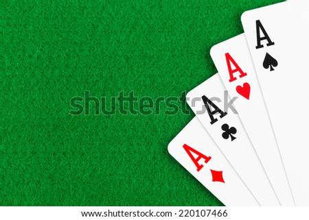 Four aces poker playing card on green felt background - stock photo
