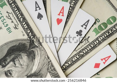 Four aces poker playing cards among U.S. dollar banknotes - stock photo