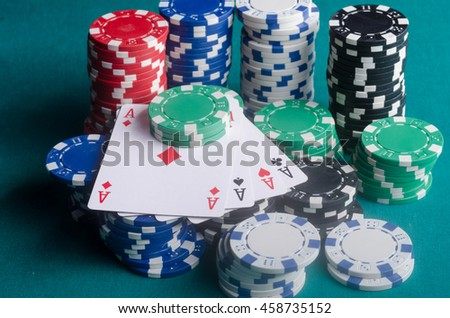 Four aces with a lot of chips on the poker table. - stock photo