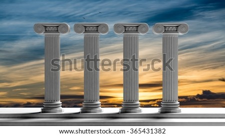 Four ancient pillars with sunset sky background. - stock photo