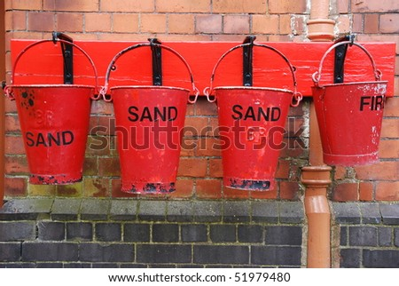 four antique fire buckets on hooks at a train station (brick wall background)