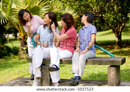 Four Asian women sitting on a bench in a park and talking - stock photo