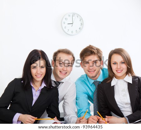 four attractive positive happy smile young business people at desk office, businesspeople meeting looking at camera, concept of team, working together.