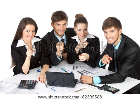 four attractive positive young business people in elegant suits sitting at desk with papers, document working in team together executives all pointing finger at you, Isolated over white background