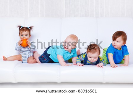 Four baby friends sit and lie on  white sofa - stock photo