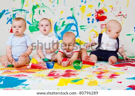 Four barefoot babies playing with paints - stock photo