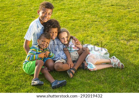 Four beautiful children are playing on the sunny glade with a smile and have fun.