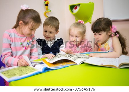 Four beautiful children are reading books at the table.