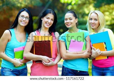 four beautiful college students  posing outside in green park - stock photo