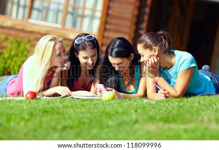 four beautiful girls chatting in social network on green lawn - stock photo