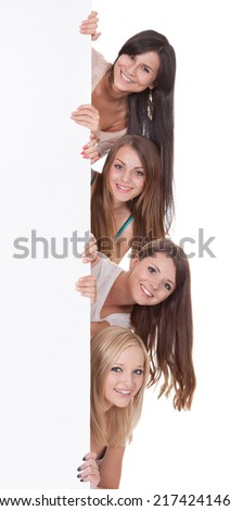 Four beautiful long-haired women peering around the edge at a blank sign with copyspace for your text - stock photo