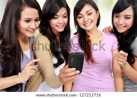 four beautiful young women friends at home using mobile phone together