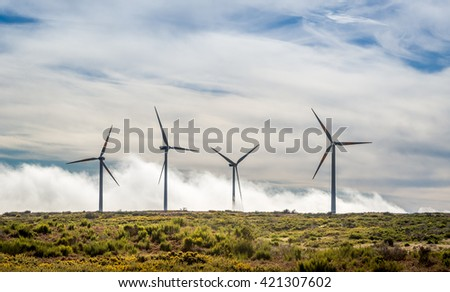 Four big wind generators in the mountain field over the clouds. Madeira island, ER105 road, Portugal.