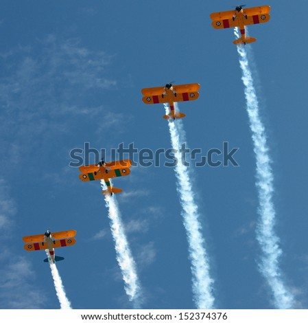 Four Biplanes with Smoke Climbing - stock photo