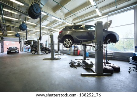 Four black cars in garage with special equipment prepared for repair. - stock photo