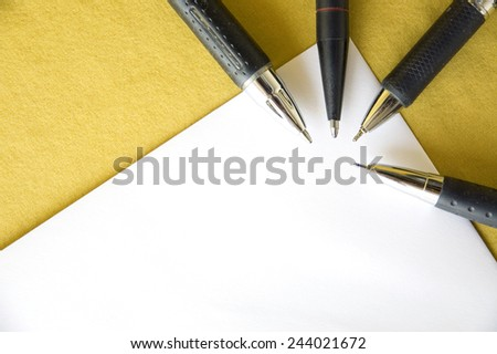 four black pen point to angle of paper on yellow background - stock photo