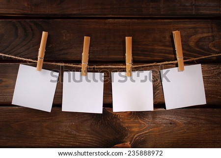four blank paper cards hanging on rope with bamboo clothespins against old wooden background  - stock photo